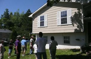image of a group of 9 course participants standing outside of two story house on a sunny day